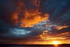 火热,明亮,沿皮吉特湾海岸的日落 免版税库存照片