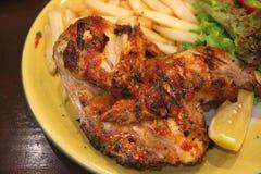 火焰板材烤了与柠檬和蔬菜沙拉片断的辣鸡  免版税库存图片