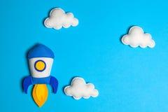 火箭队离开 与白色云彩的太空船在蓝色背景 手工制造毛毡玩具 免版税库存图片
