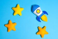 火箭队离开 手工制造毛毡玩具 与黄色星的太空船在蓝色背景 免版税库存照片