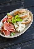 火腿、乳酪、蕃茄和ciabatta面包在一块卵形板材黑暗的木表面上 库存图片