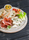 火腿、乳酪、蕃茄和ciabatta面包在黑暗的木表面上的一个轻的木板服务 免版税图库摄影