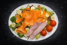 火腿、蕃茄、红萝卜、香蕉、火箭、莴苣绿橄榄和葡萄健康沙拉  图库摄影