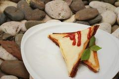 火腿和乳酪三明治用在一块白色板材的调味汁 库存照片