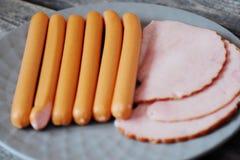 火腿和香肠在一块板材在桌上 图库摄影