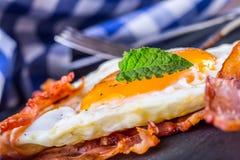火腿和鸡蛋 烟肉和鸡蛋 盐味的鸡蛋和洒与黑胡椒和绿色草本装饰 免版税图库摄影