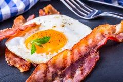 火腿和鸡蛋 烟肉和鸡蛋 盐味的鸡蛋和洒与黑胡椒和绿色草本装饰 免版税库存照片