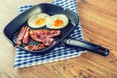 火腿和鸡蛋 烟肉和鸡蛋 盐味的鸡蛋和洒与黑胡椒 烤烟肉,在聚四氟乙烯平底锅的两个鸡蛋 免版税库存照片