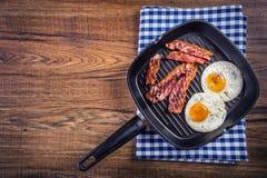 火腿和鸡蛋 烟肉和鸡蛋 盐味的鸡蛋和洒与黑胡椒 烤烟肉,在聚四氟乙烯平底锅的两个鸡蛋 免版税图库摄影