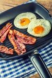 火腿和鸡蛋 烟肉和鸡蛋 盐味的鸡蛋和洒与黑胡椒 烤烟肉,在聚四氟乙烯平底锅的两个鸡蛋 库存图片