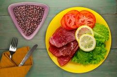 火腿用沙拉、蕃茄和柠檬在板材 免版税库存照片