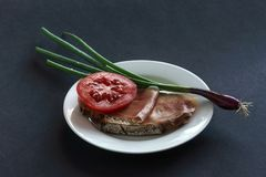 火腿面包用蕃茄和韭葱在板材,灰色背景 库存照片