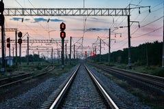 火车光和基础设施在美好的日落、五颜六色的天空、运输和工业概念期间 免版税库存图片