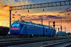 火车和无盖货车、铁路基础设施、美好的日落和五颜六色的天空、运输和工业概念 库存照片