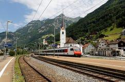 火车在弯曲通过有教会的瑞士村庄的铁路移动山坡和庄严高山山的 免版税库存照片