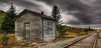 火车在秋天接近房屋板壁 免版税图库摄影