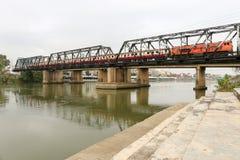 火车在Ratchaburi,泰国遇到朱拉隆功铁路桥 免版税图库摄影