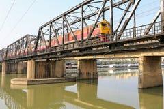 火车在Ratchaburi,泰国遇到朱拉隆功铁路桥 免版税库存图片