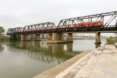 火车在Ratchaburi,泰国遇到朱拉隆功铁路桥 免版税库存照片