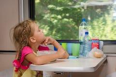 火车的一个六年女孩在桌上用食物坐汽车和神色你的第二等的隔间的一个更低的地方 免版税库存图片
