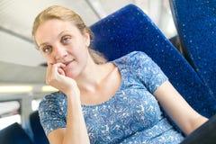妇女考虑某事在火车 免版税库存照片