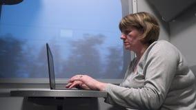 火车的妇女与膝上型计算机一起使用 股票录像