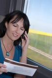 火车的妇女谈话在电话微笑 免版税库存图片