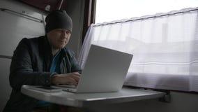 火车的年轻人有他的膝上型计算机的 影视素材