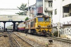 火车离开起源曼谷驻地通过破旧商业的大厦 图库摄影