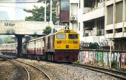 火车离开起源曼谷驻地通过破旧商业的大厦 免版税库存图片
