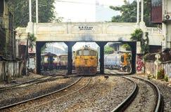 火车离开起源曼谷驻地通过破旧商业的大厦 免版税库存照片