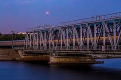 火车穿过铁路桥,长的曝光 在天空的月亮蚀 免版税图库摄影