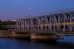 火车穿过铁路桥 在天空的月亮蚀 库存照片