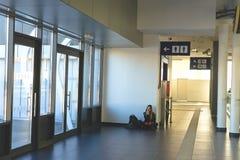 火车站的大厦的孤独的旅客 女孩耳机听的音乐 图库摄影