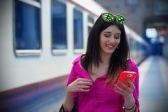火车站的好女孩与她的智能手机 免版税库存图片