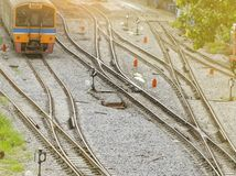 火车轨道和交通标志在铁路之间 乘火车远航与温暖的日出光的早晨 局部运输 免版税库存图片