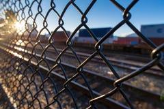 火车轨道通过在日落的chainlink篱芭 免版税库存照片