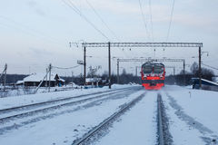 火车通过传统俄国村庄跟随在冬天 免版税图库摄影