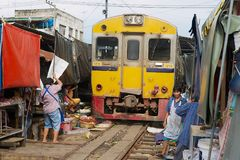 火车通过Mae Klong铁路轨道市场在Samut Songkram,泰国 免版税库存图片