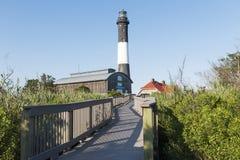 火从木板走道入口的海岛灯塔 免版税库存图片