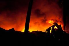 灭与巨大的火焰的消防员剪影发怒的火 免版税库存照片