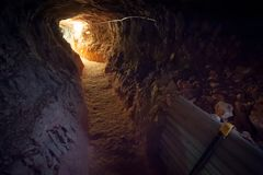 灯不足点燃的昏暗的隧道在末端 库存照片