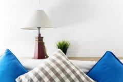 灯和绿色植物床边的有蓝色和灰色pollows的 酒店房间内部背景 免版税库存照片