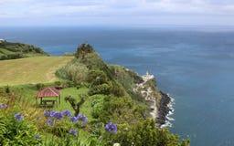 灯塔、庭院房子和大西洋的一个引人入胜的看法在Nordeste附近村庄在圣米格尔火山海岛上  免版税库存照片