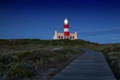 灯塔光亮的光在与深蓝云彩的黑暗中 免版税库存照片