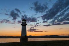 灯塔和日落在一个湖有云彩的 图库摄影