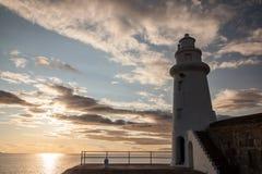 灯塔和日落在海 免版税库存照片