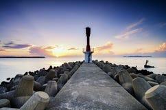 灯塔和美丽的海观看在惊人的日出背景的风景 免版税库存图片