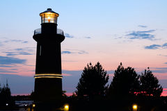 灯塔现出轮廓在日落 库存图片