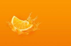 幻灯片削减了橙色下落片断在橙色背景的用桔子 库存照片